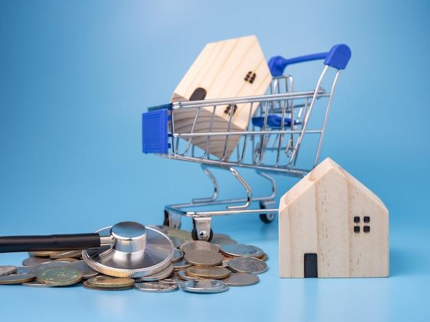 Um modelo de casa de madeira no carrinho de compras com uma pilha de moedas e um estetoscópio no azul