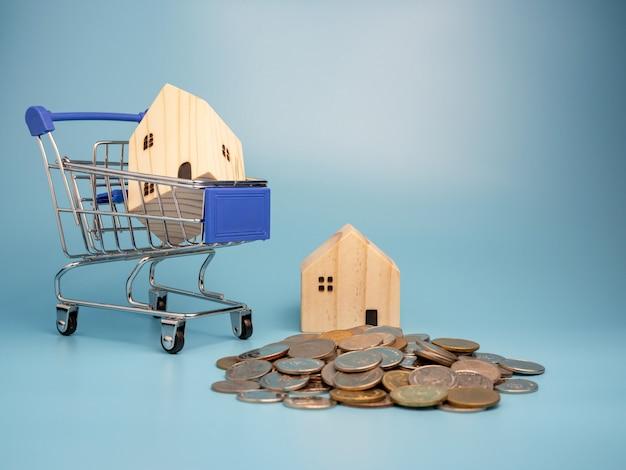 Um modelo de casa de madeira no carrinho de compras com uma pilha de moedas no azul