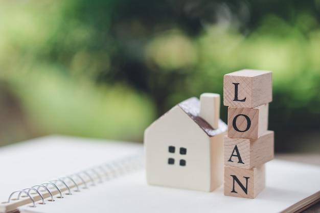 Um modelo de casa modelo é colocado em uma pilha de moedas de madeira palavra empréstimo