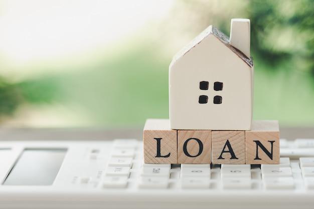 Um modelo de casa modelo é colocado na palavra madeira loan