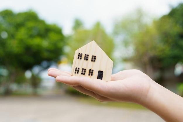 Um modelo de casa modelo é colocado nas mãos da garota de negócios asiática. conceito
