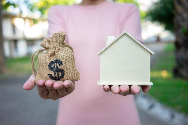 Um modelo de casa modelo é colocado nas mãos da menina asiática do negócio.