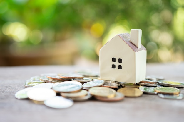 Um modelo de casa modelo é colocado sobre uma pilha de coins.using como conceito de negócio em segundo plano