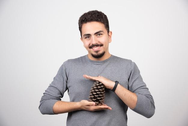 Um modelo de homem sorridente segurando uma pinha.