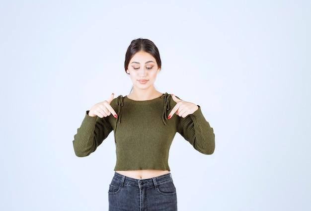 Um modelo de jovem em pé e apontando para baixo com os dedos.