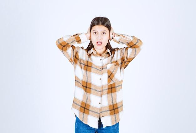 Um modelo de jovem em pé e cobrindo as orelhas.
