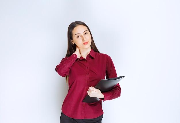 Um modelo de menina morena em pé e posando com uma pasta contra uma parede branca.