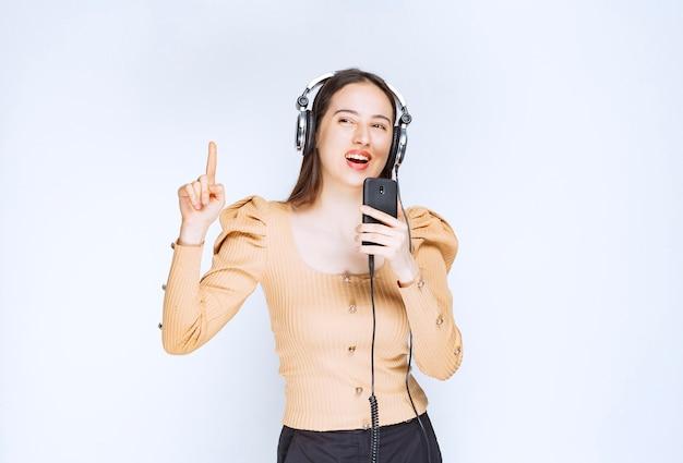 Um modelo de mulher atraente ouvindo música em fones de ouvido e apontando para cima.