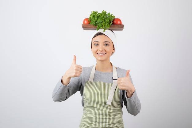 Um modelo de mulher com uma placa de madeira de legumes frescos na cabeça aparecendo os polegares.