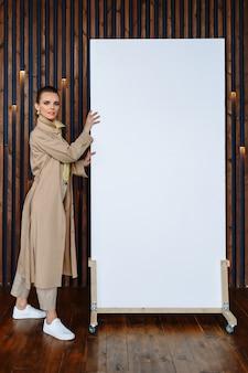 Um modelo de mulher em uma capa de chuva bege mostra uma tela branca na qual você pode escrever um slogan ou informações de publicidade