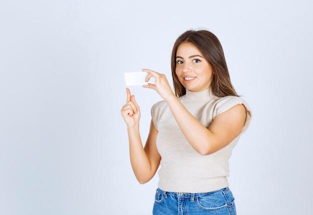 Um modelo de mulher feliz segurando um cartão e posando.