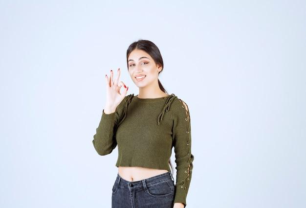 Um modelo de mulher jovem bonita piscando e mostrando o gesto de ok.