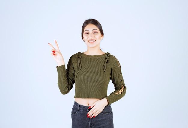 Um modelo de mulher jovem sorridente em pé e mostrando sinal de vitória.