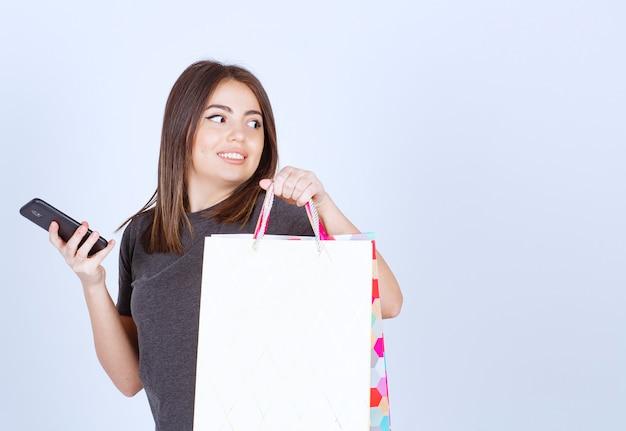 Um modelo de mulher sorridente carregando um monte de sacolas de compras e segurando um telefone.