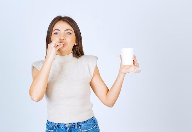 Um modelo de mulher sorridente, mostrando um copo de plástico e posando.