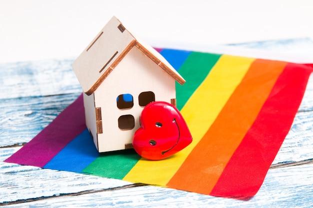 Um modelo de uma pequena casa de madeira e um coração na bandeira das cores do arco-íris