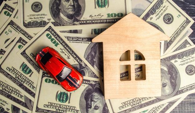 Um modelo e um carro de madeira da casa com dólares americanos. compra e venda ou seguro de carro.