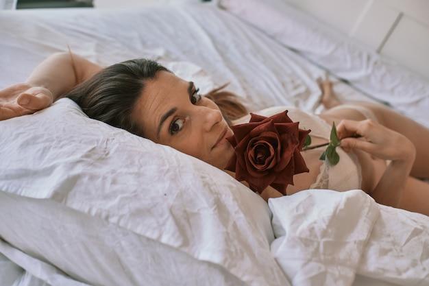 Um modelo encontra-se na cama dela