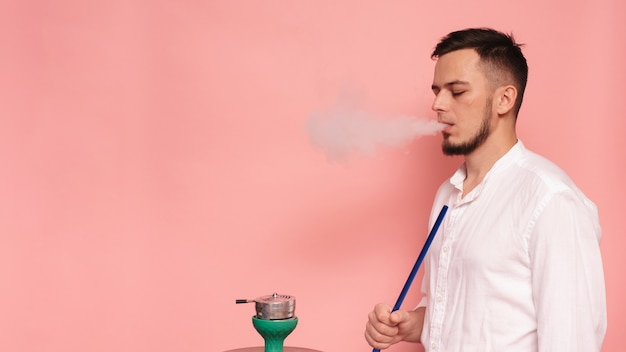 Um modelo masculino fuma narguilé, sheesha e se diverte.