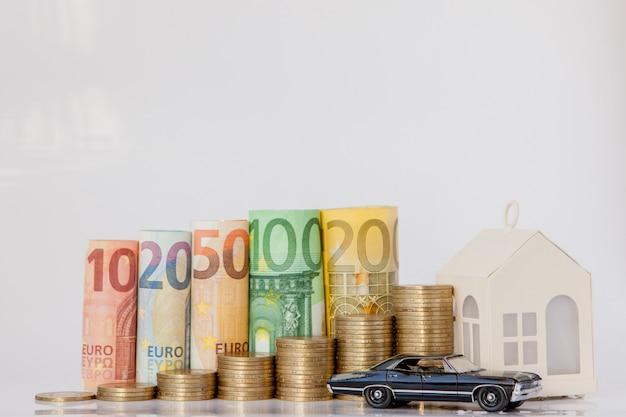 Um modelo preto de carro, casa e dez, vinte, cinquenta, cem, duzentos e moedas de euro rolou notas de banco em fundo branco. histograma do euro. conceito de crescimento da moeda, poupança.