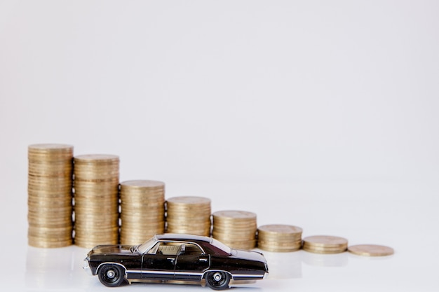 Um modelo preto de um carro com moedas na forma de um histograma sobre um fundo branco. conceito de empréstimo, poupança, seguro.