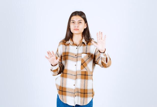 Um modelo sério jovem em pé e mostrando o sinal de stop.