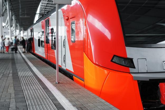 Um moderno trem elétrico de alta velocidade fica em uma plataforma.