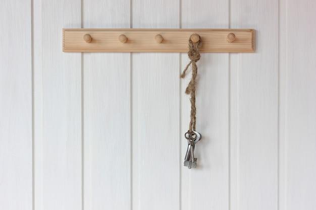 Um molho de chaves está pendurado em um cabide na parede branca