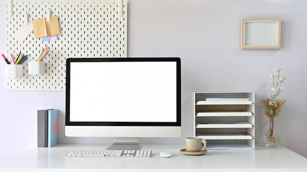 Um monitor de computador no espaço de trabalho está sobre uma mesa de trabalho branca, cercada por equipamentos de escritório.