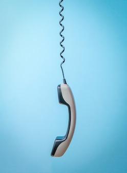 Um monofone cinza em um fio de telefone esticado em um fundo azul.