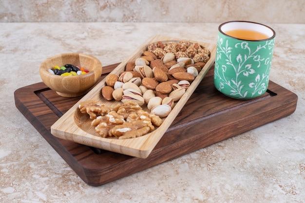 Um monte de amêndoas de nozes em um prato de madeira com chá quente