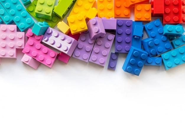 Um monte de blocos coloridos construtor plastick em madeira branca