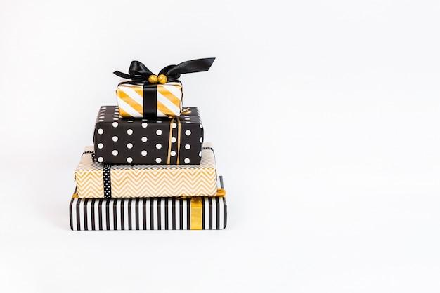Um monte de caixas de presente em várias cores preto, branco e dourado