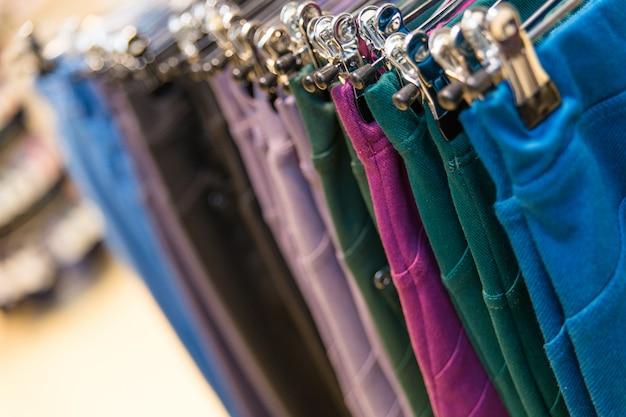 Um monte de calças jeans coloridas penduradas em cabides em uma loja de roupas