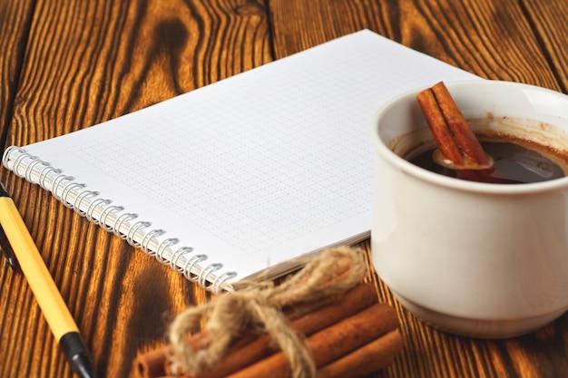 Um monte de canela de malha com uma corda, uma xícara de café e um caderno para escrever