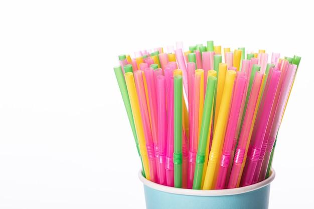 Um monte de canudos de plástico multicoloridos em um copo descartável de papel biodegradável