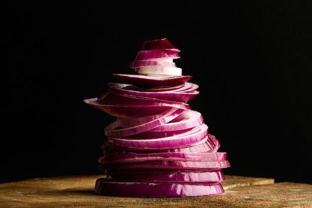 Um monte de cebola roxa fatiada em uma mesa de madeira com um fundo escuro