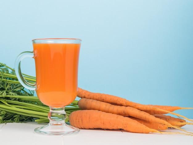 Um monte de cenouras e um copo de smoothies em uma mesa branca sobre um fundo azul.