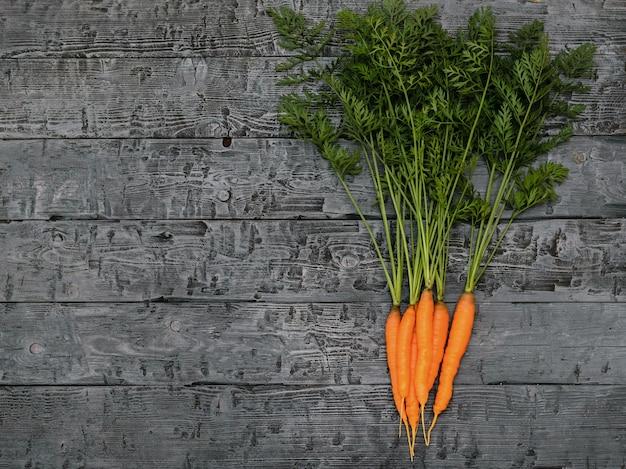 Um monte de cenouras frescas e ervas em uma mesa rústica preta