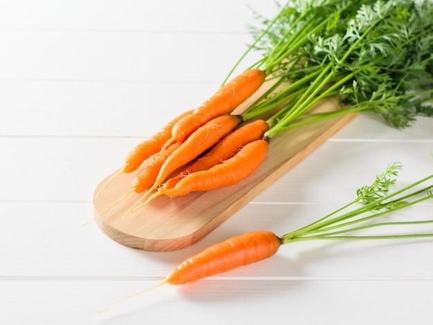 Um monte de cenouras frescas em uma tábua e uma cenoura em uma mesa de madeira branca.