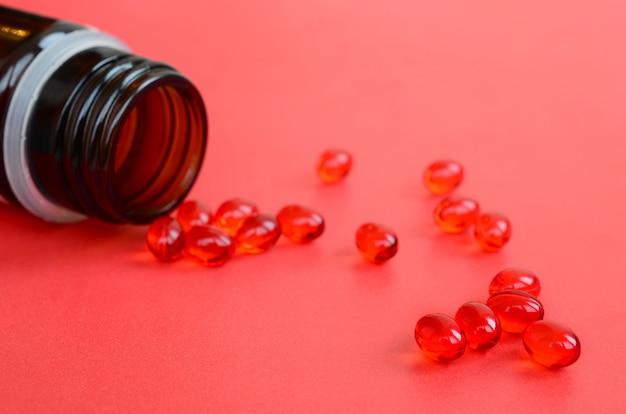 Um monte de comprimidos vermelhos transparentes foram espalhados de um pequeno frasco de vidro marrom em uma superfície vermelha