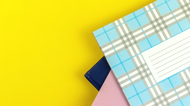 Um monte de diário escolar sobre fundo de mesa amarelo brilhante, foto de vista superior com espaço de cópia
