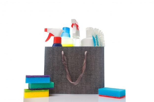 Um monte de diferentes materiais de limpeza e produtos de limpeza doméstica em um saco de papel
