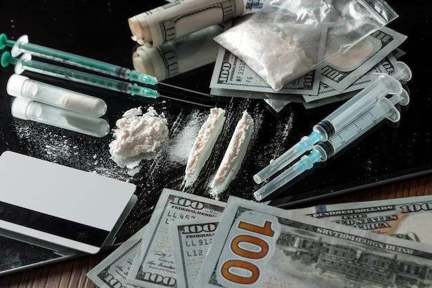 Um monte de drogas diferentes com seringas e comprimidos em uma tabela