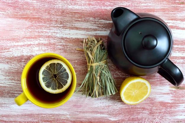 Um monte de erva-cidreira, limão fresco, bule e xícara de chá.