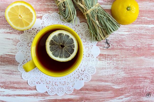 Um monte de erva-cidreira, limão fresco e uma xícara de chá.