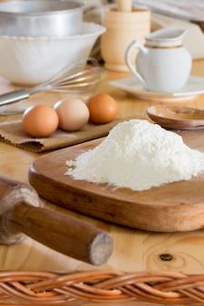 Um monte de farinha de trigo branca, ovos crus, rolo, batedor de aço inoxidável e outros utensílios na mesa da cozinha.