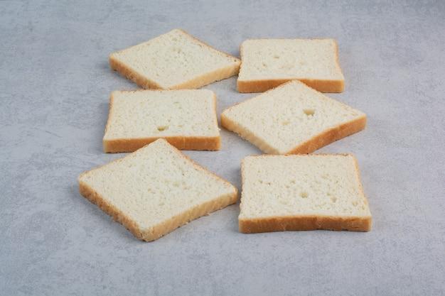 Um monte de fatias de pão na superfície da pedra