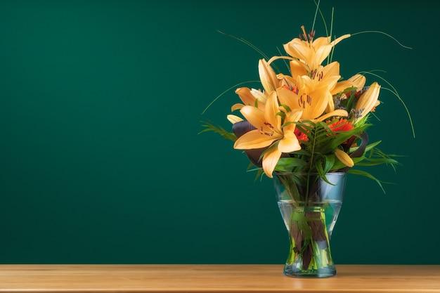 Um monte de flores de lírio amarelo em um vaso em uma mesa contra uma parede verde