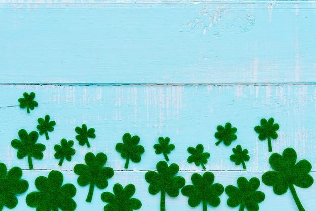 Um monte de folha de trevo de papel verde na mesa de madeira branca e azul pastel